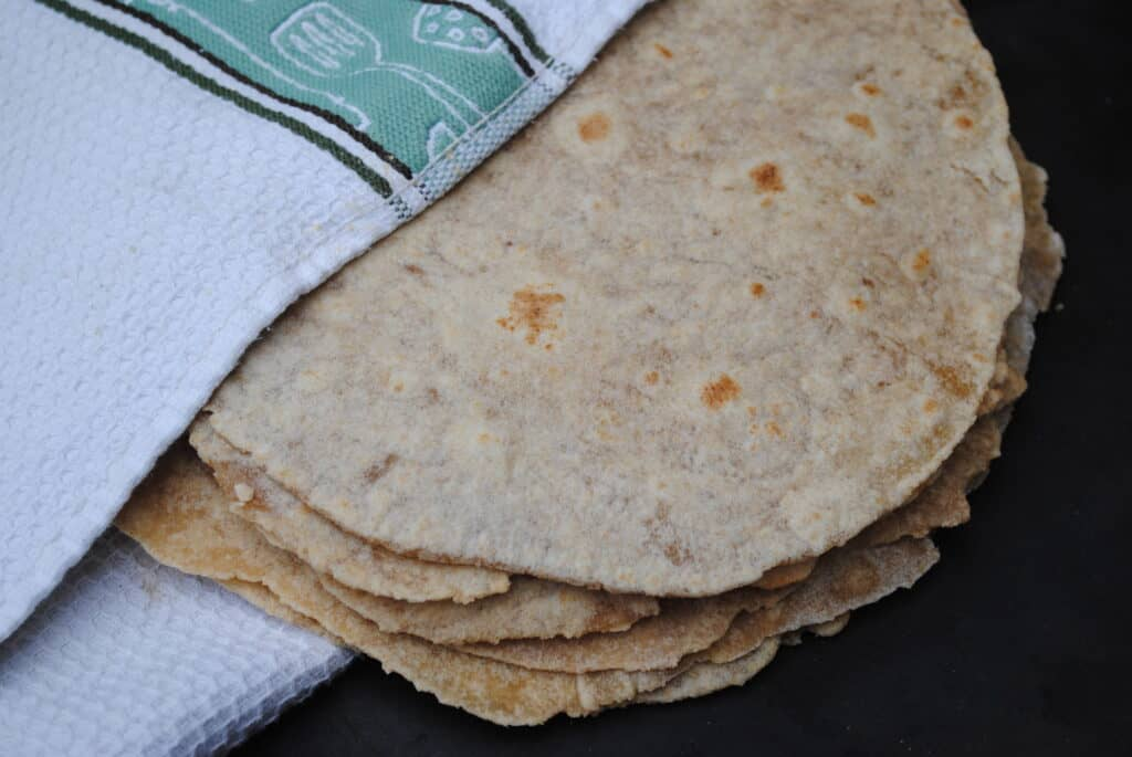 homemade whole wheat tortillas wrapped in a towel
