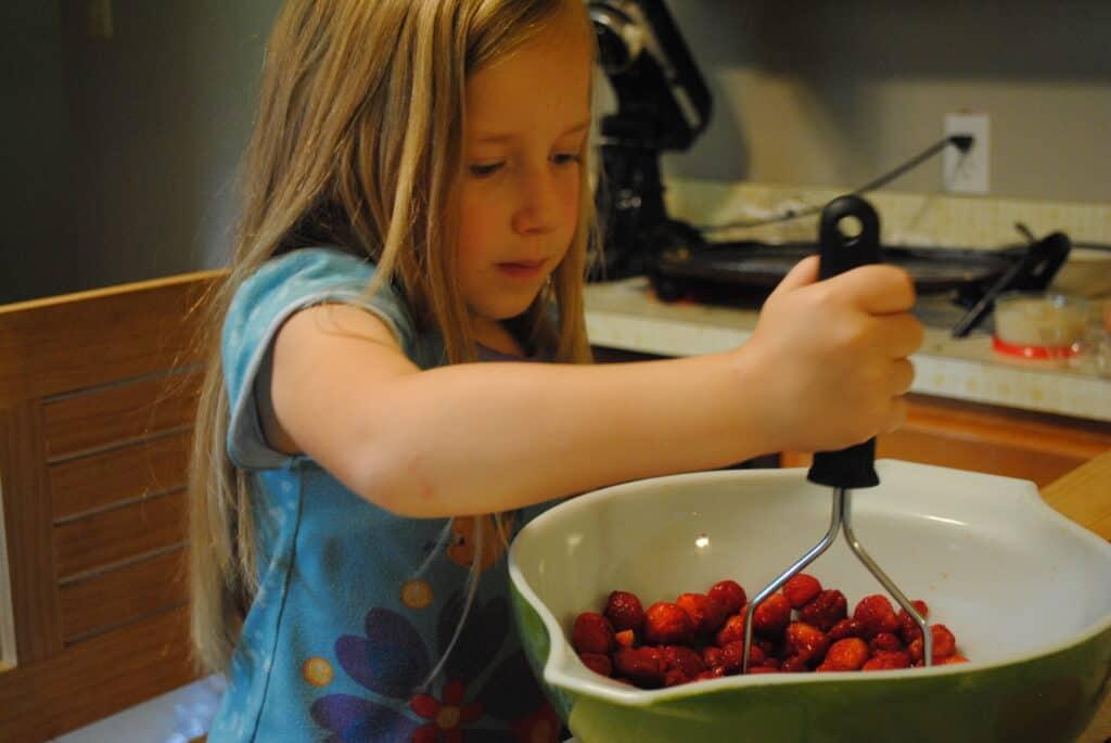 girl smashing berries in a bowl