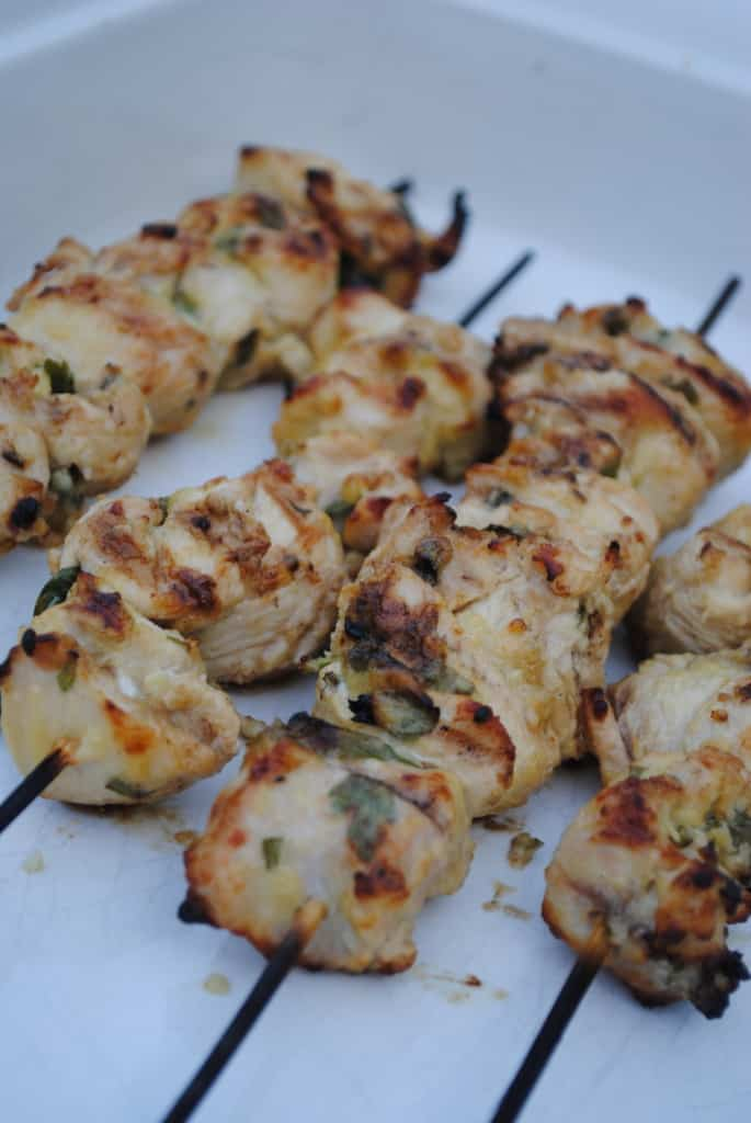 Lemon herb chicken kabobs in a white dish