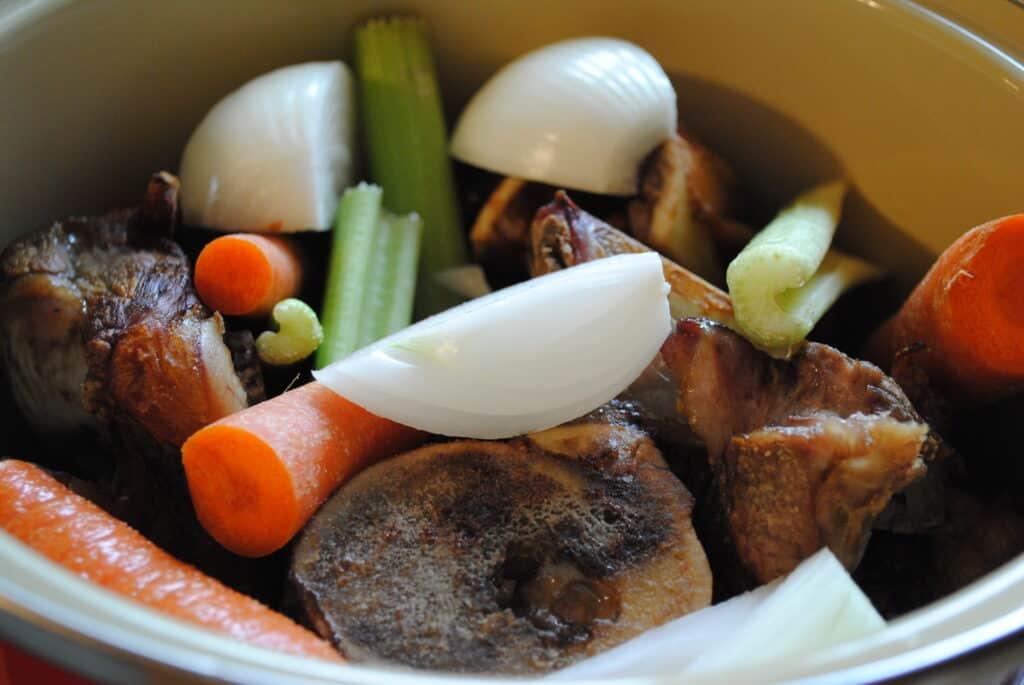 beef bones and vegetables in a pot