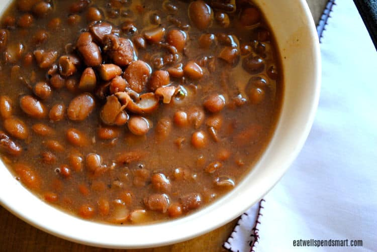slow cooked pinto beans in a white bowl with a white napkin beside it
