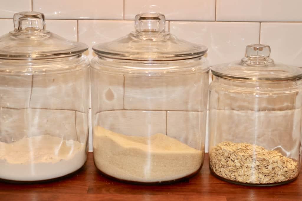 Glass jars of flour, sugar, and oats