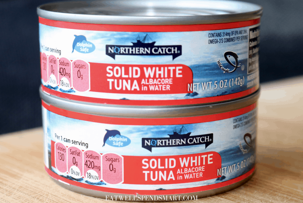 Two cans of tuna on a wooden board