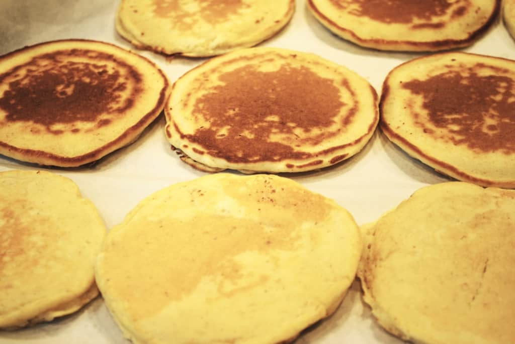 flash freezing pancakes flat in a single layer on a a parchment lined baking sheet