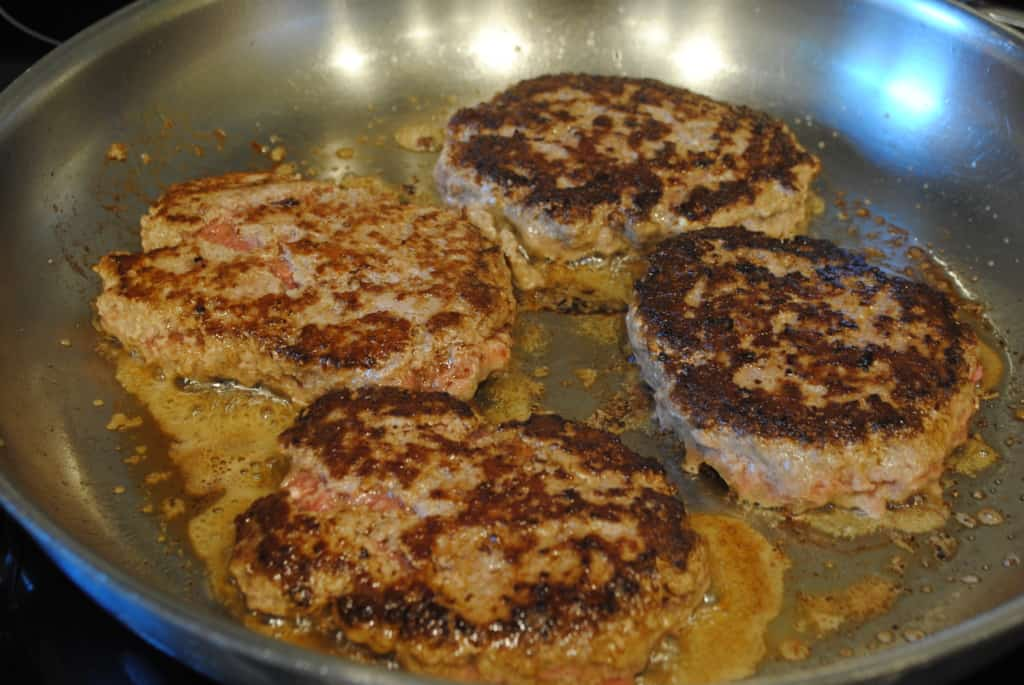 Ground beef patties browning in a skillet.