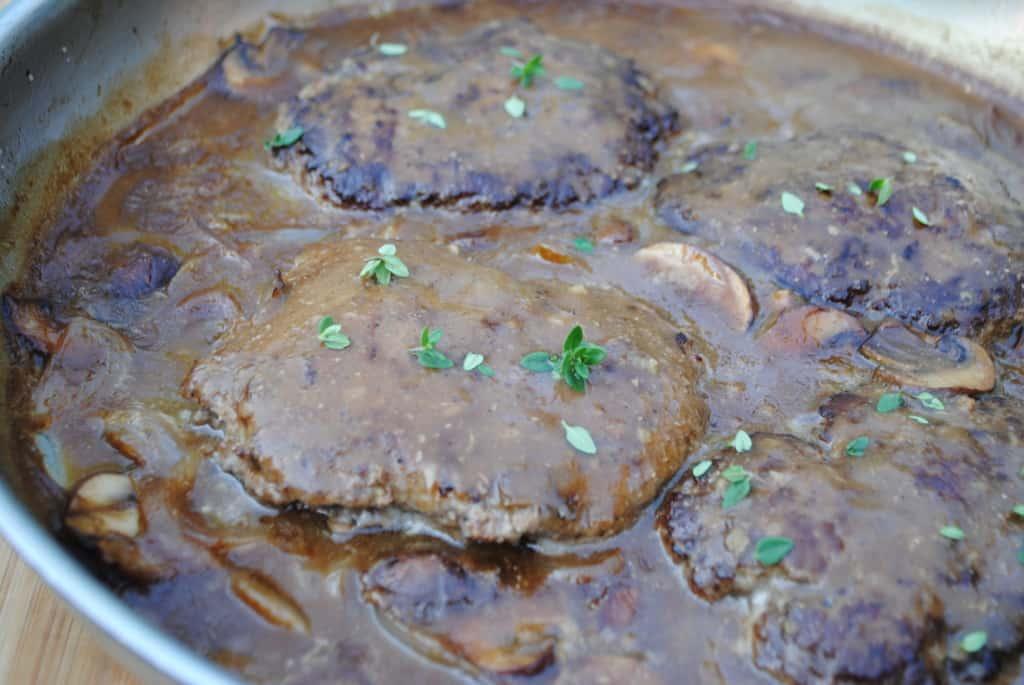 Ground beef patties in an onion and mushroom brown gravy.