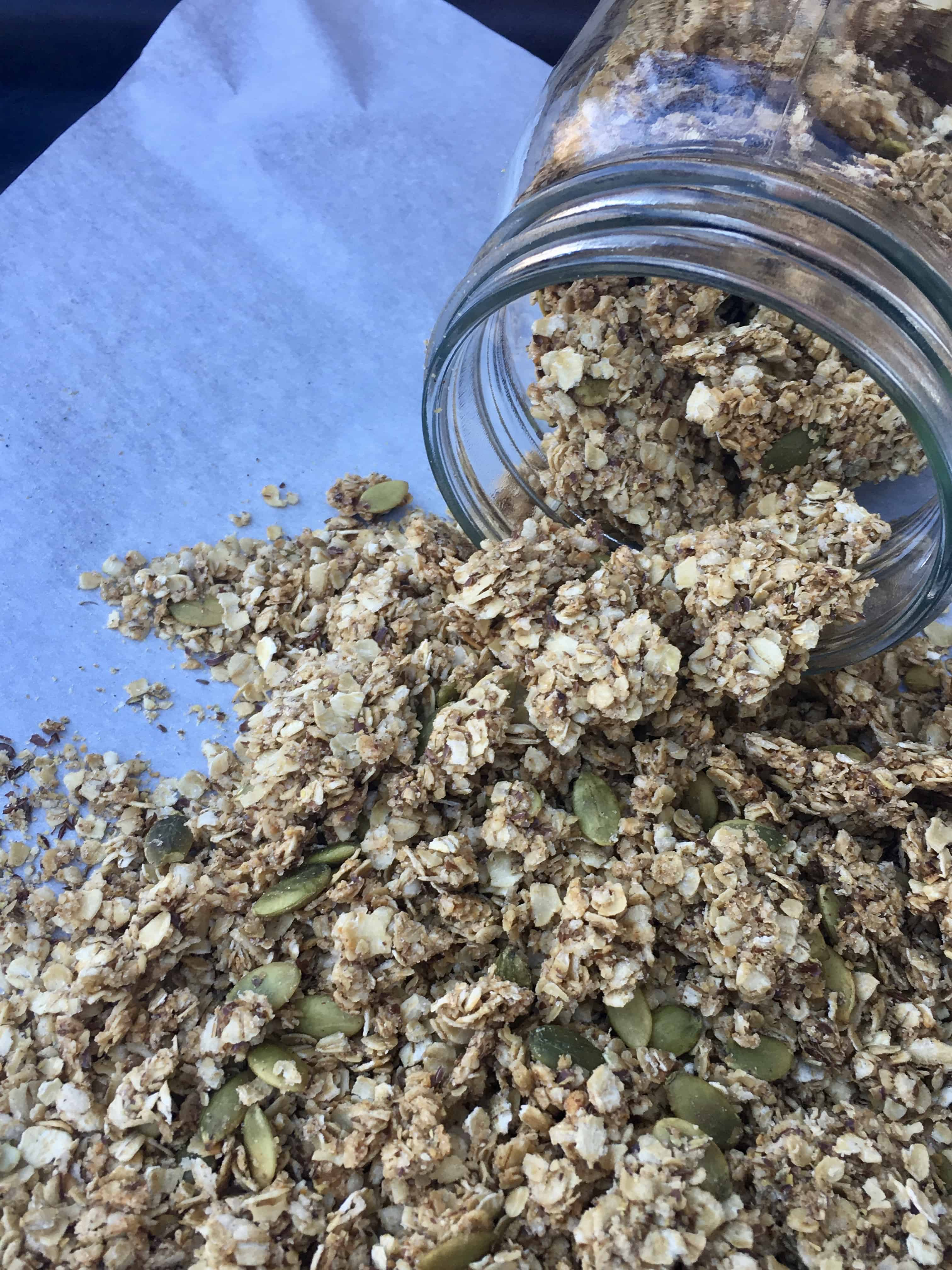jar of granola spilling onto parchment paper