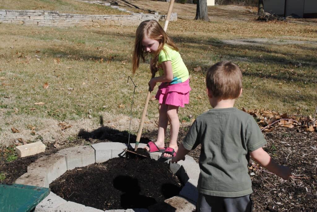 Girl spreading garden soil