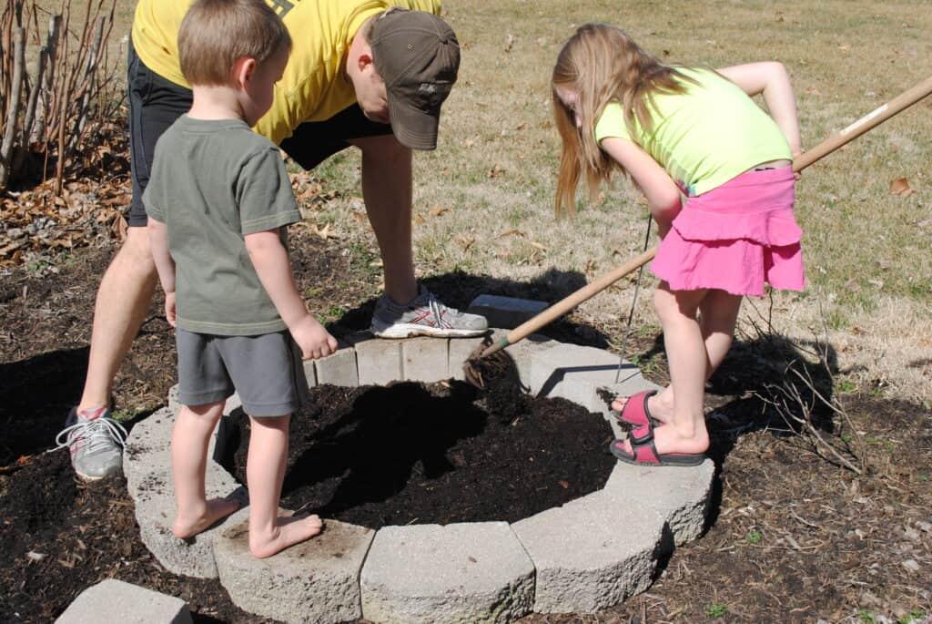 Girl spreading garden soil while man and boy watch