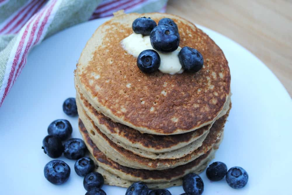 oat pancakes on a white plate and topped with blueberries