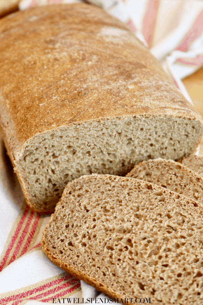A loaf of homemade bread with two cut bread slices on board