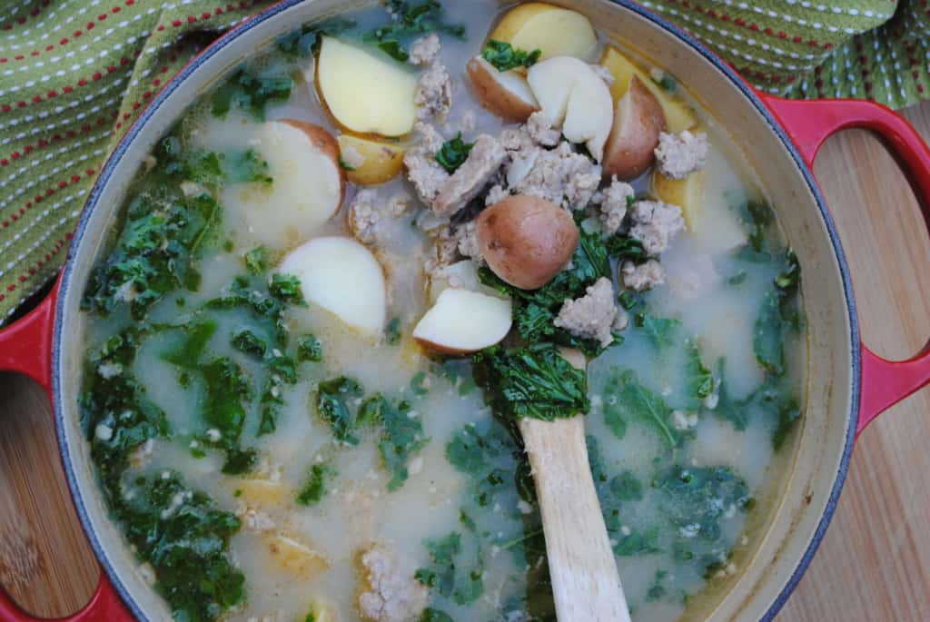 wooden spoon scooping out sausage, kale, and potato soup from a pot
