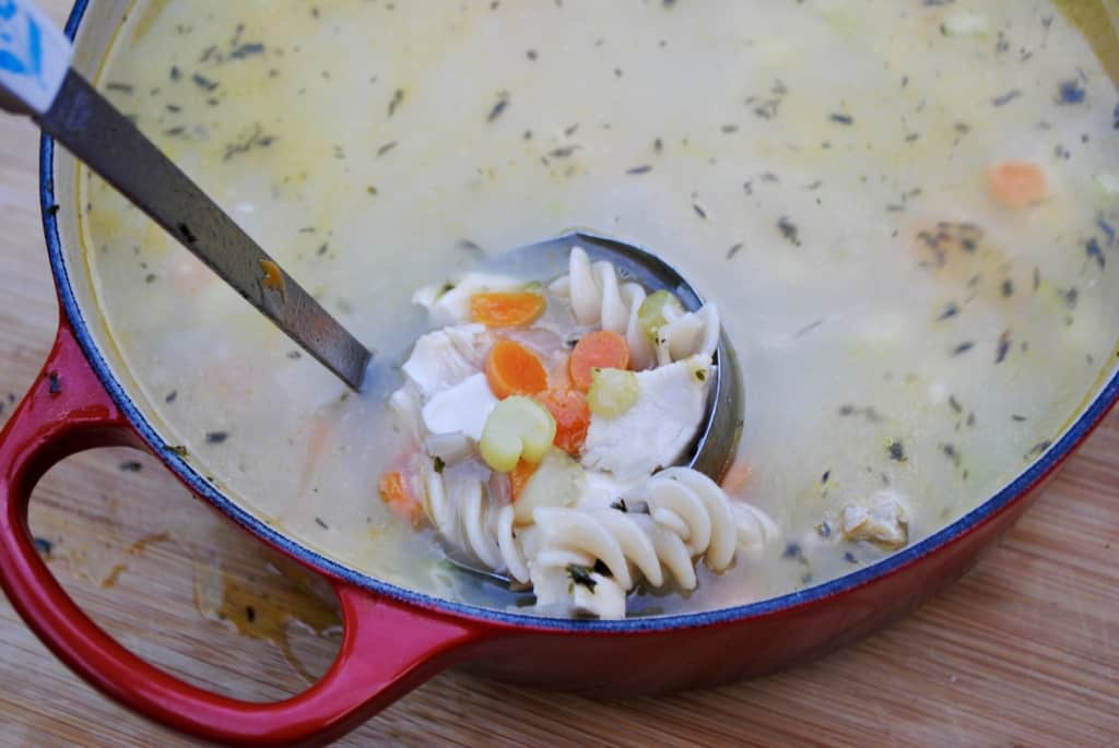 Ladle scooping chicken noodle soup out of a red pot