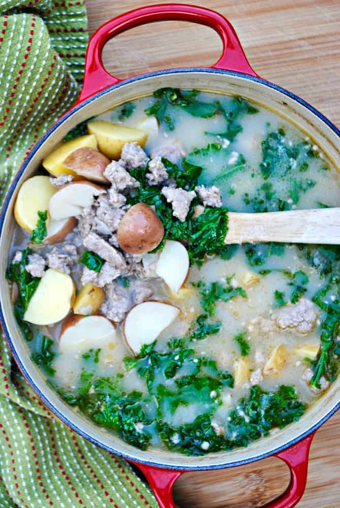 A wooden spoon scooping out sausage, potato, and kale soup from red pot