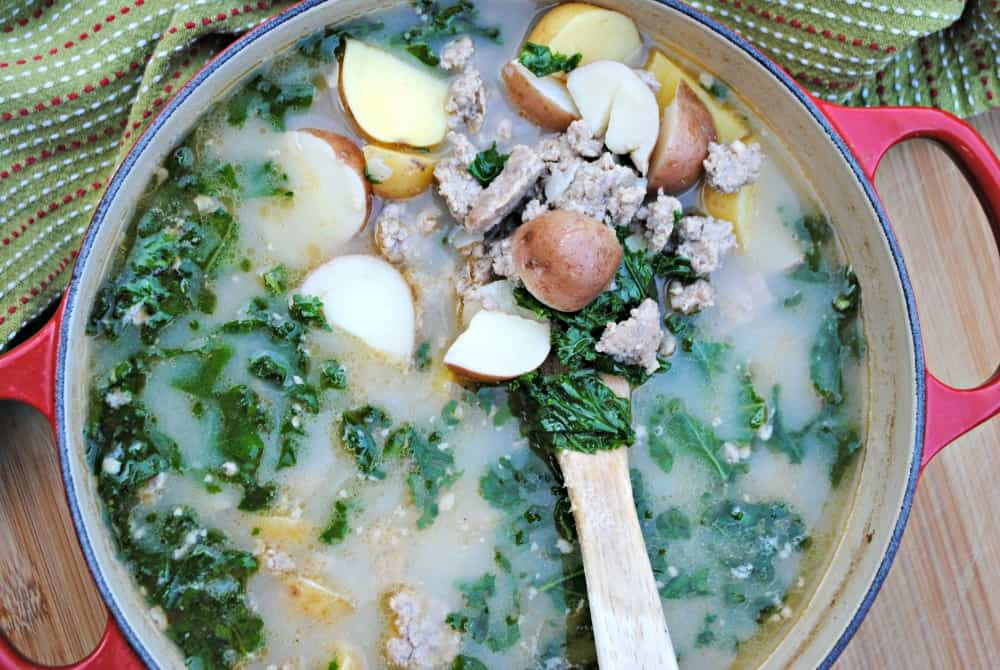 A stock pot full of Zuppa Toscana: a creamy sausage, kale, and potato soup