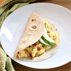 breakfast tacos on a white plate next to a green towel