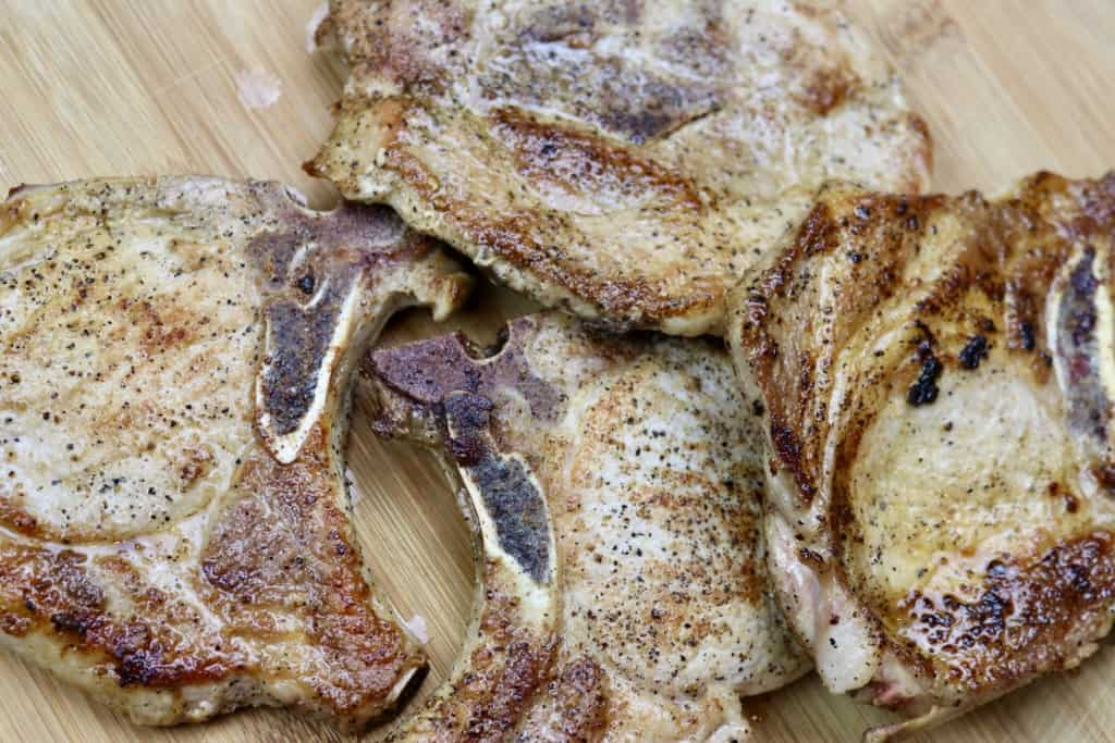 Simple skillet pork chops piled on a wooden board.