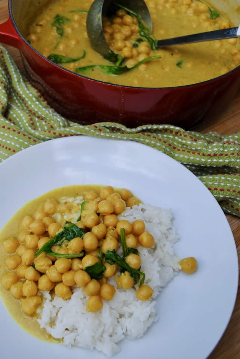 Chickpea and spinach curry with white rice on a white plate. Red pot with ladle scooping chickpea curry in background.