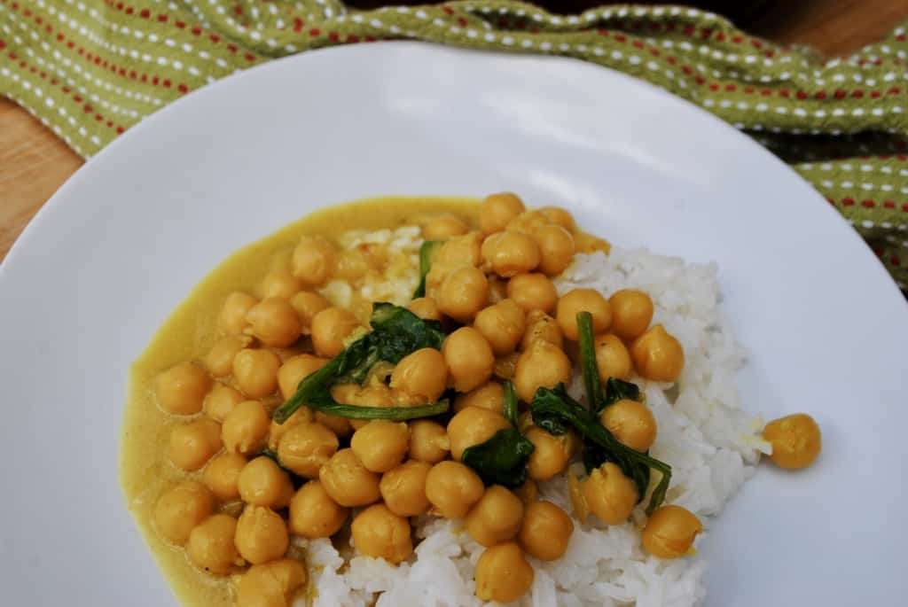 chickpea and spinach curry on a white plate beside a green towel