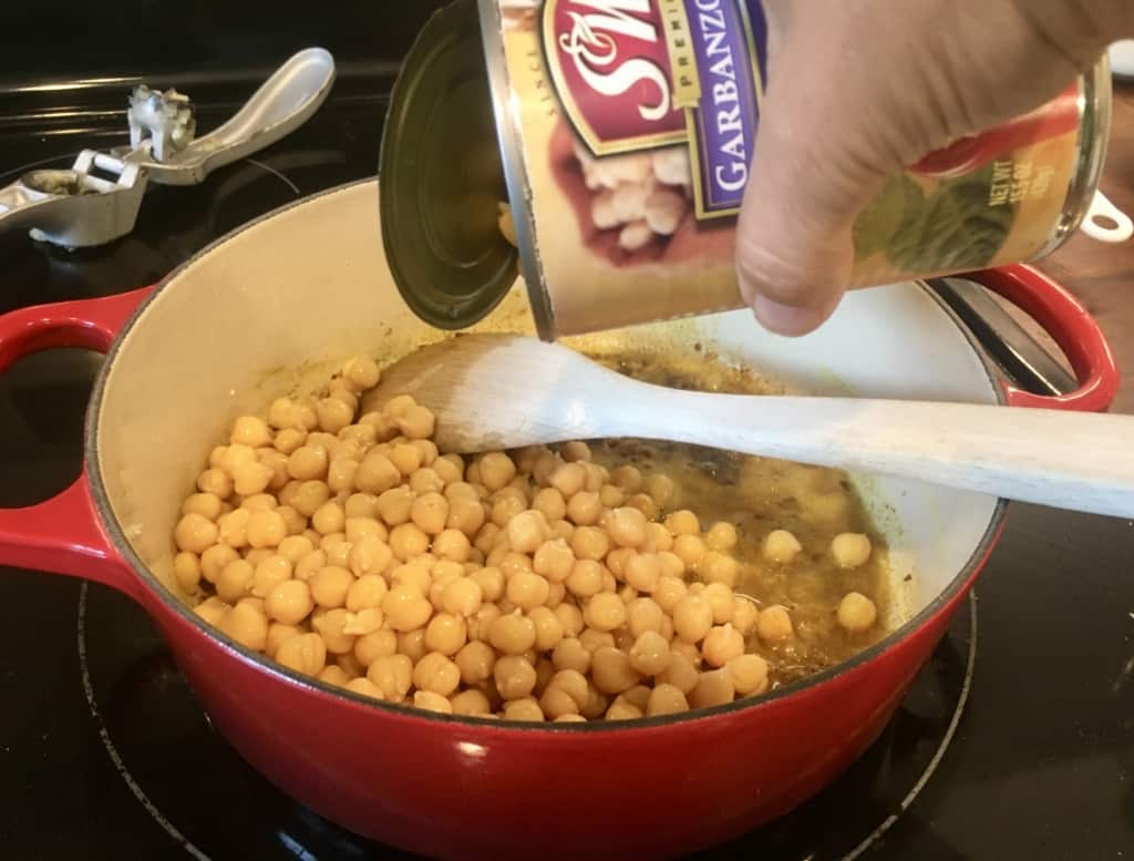 A can of chickpeas being poured into dutch oven.
