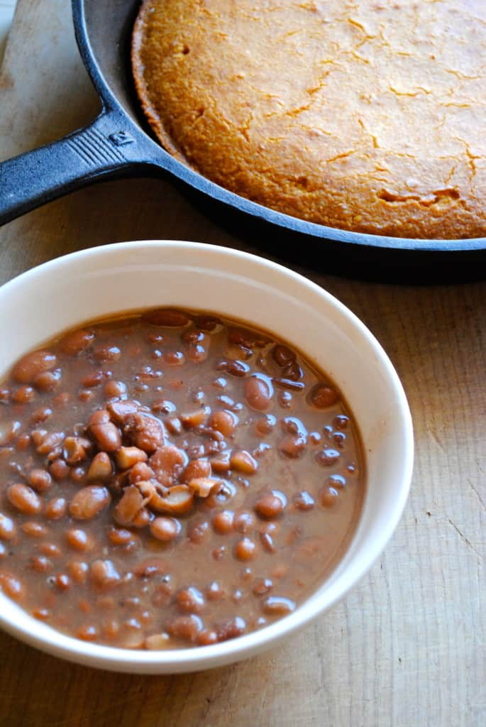 Pinto beans in a white bowl with cornbread in a cast iron skillet