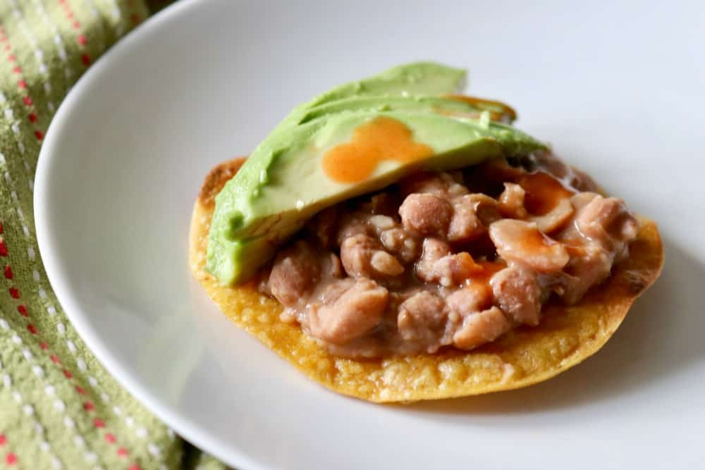Leftover pinto beans on a crunchy corn tortilla