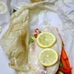 Delicate white fish filet on top of julienned vegetables and baked in a parchment packet.