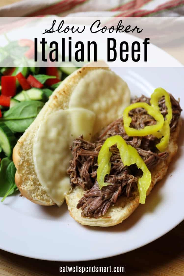 Italian beef hoagie sandwich topped with peppers on a white plate. Salad in the background.