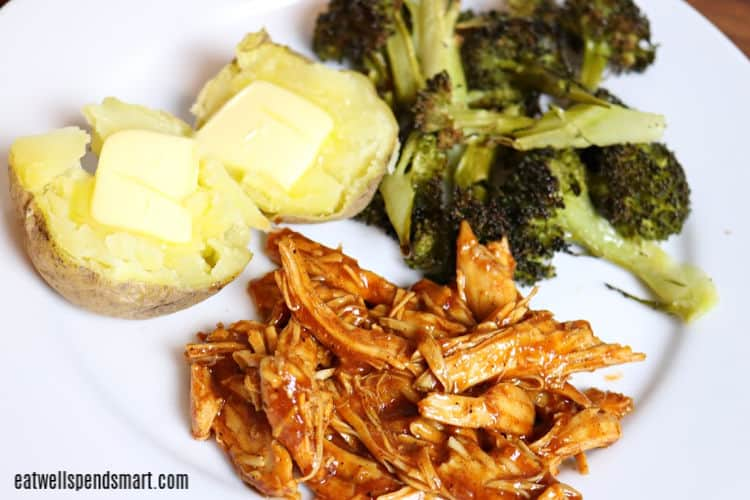 shredded bbq chicken, roasted broccoli, and baked potato with butter on a white plate