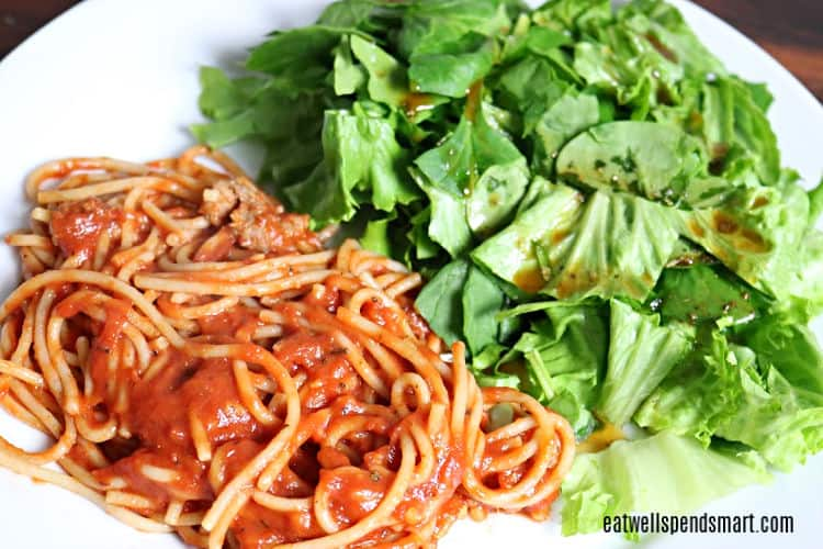 spaghetti and salad on a white plate