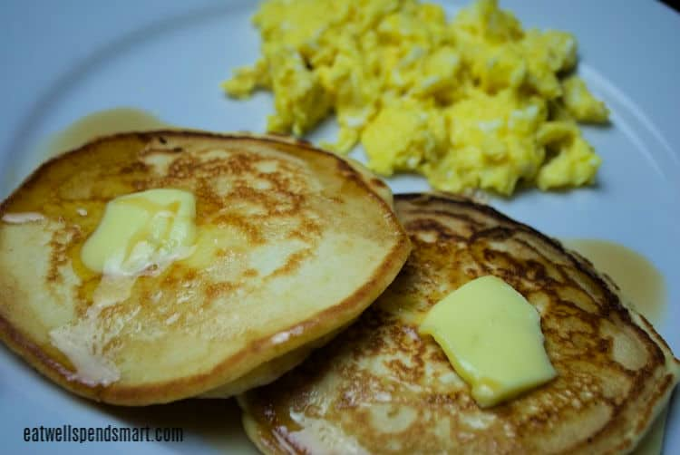 two pancakes with butter and syrup with eggs in the background on a white plate