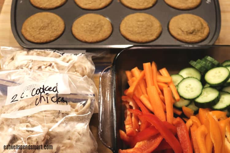 muffins, cut up veggies in a glass dish, and two bags of shredded chicken
