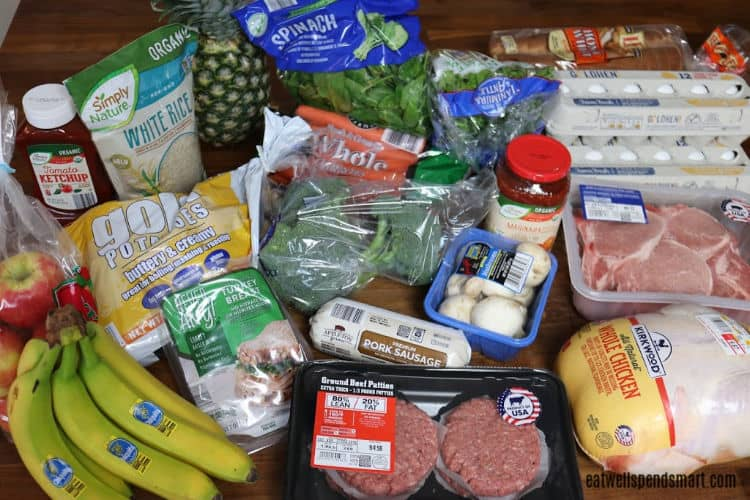 groceries on a wooden countertop: chicken, pork chops, burgers, eggs, bananas, apples, potatoes, ketchup, rice, pineapple, spinach, broccoli, mushrooms, and pasta sauce
