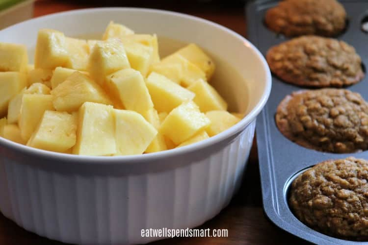 cubed pineapple in a white bowl beside pumpkin oat muffins in a muffin tin