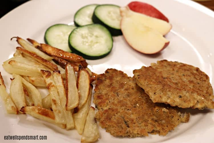 salmon patties, oven fries, apple slices, and cucumber slices on a white plate