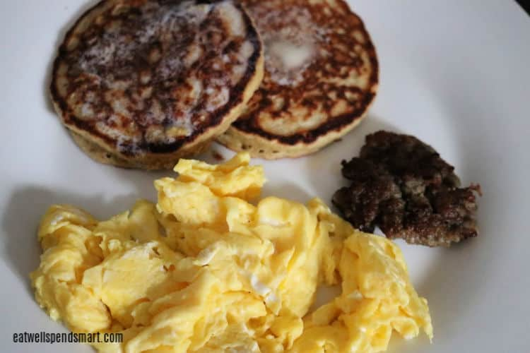 scrambled eggs, sausage, and oat pancakes on a white plate