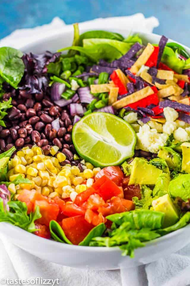 Vegetarian taco salad with black beans, corn, tomatoes, avocado, cheese, and tortillas.