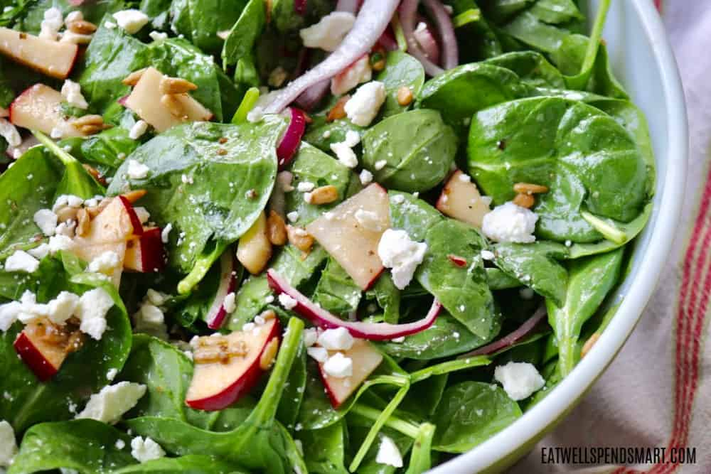 Spinach and apple salad with red onion, feta cheese, and sunflower seeds.