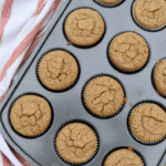 Muffins in a muffin tin with a striped towel