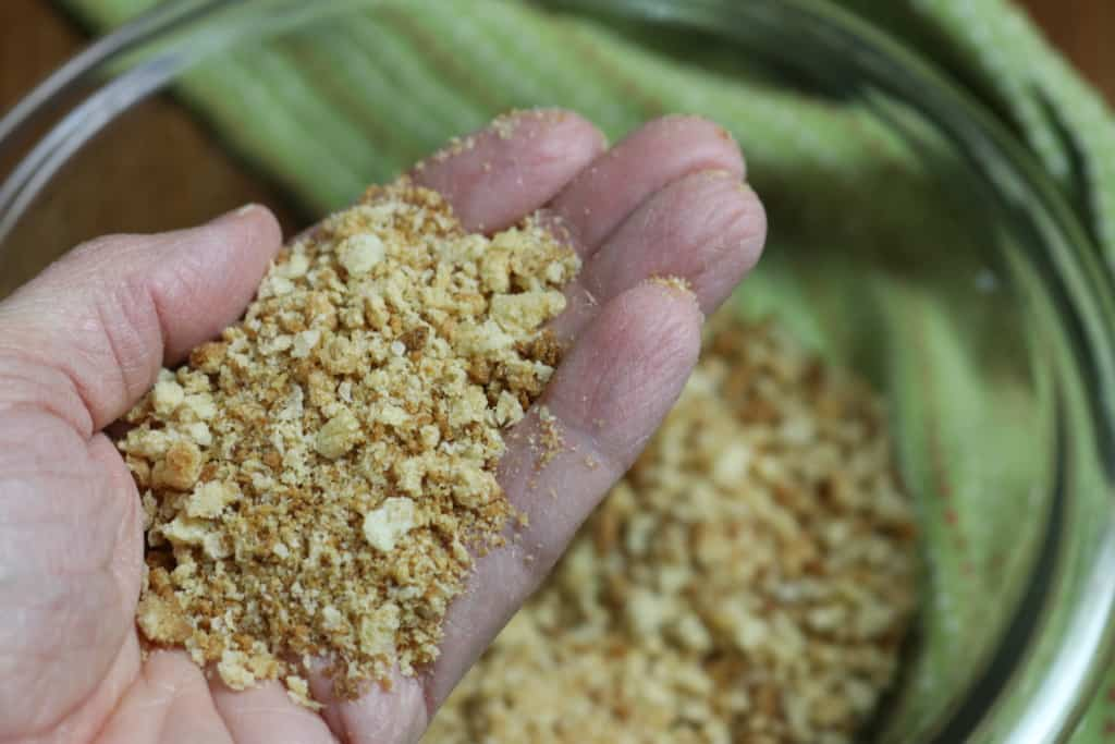 Homemade breadcrumbs in the palm of a hand.