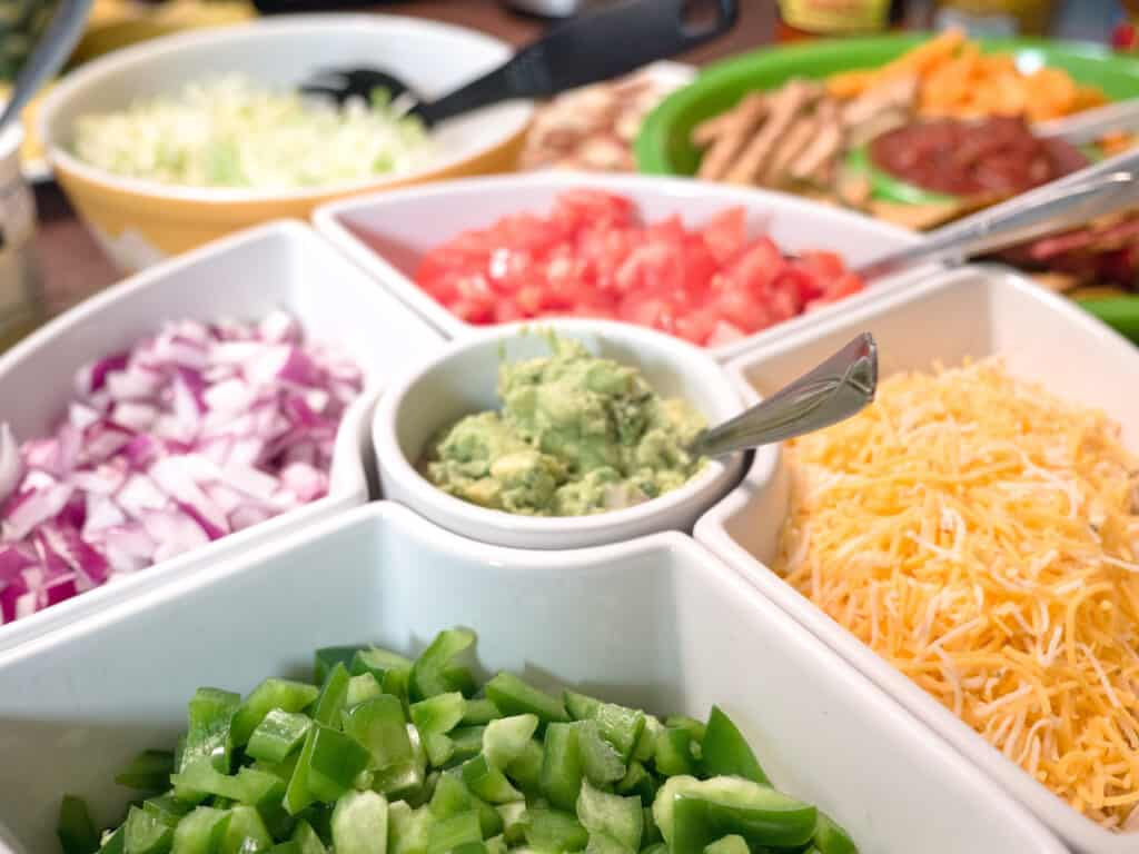taco bar toppings in a white serving dish