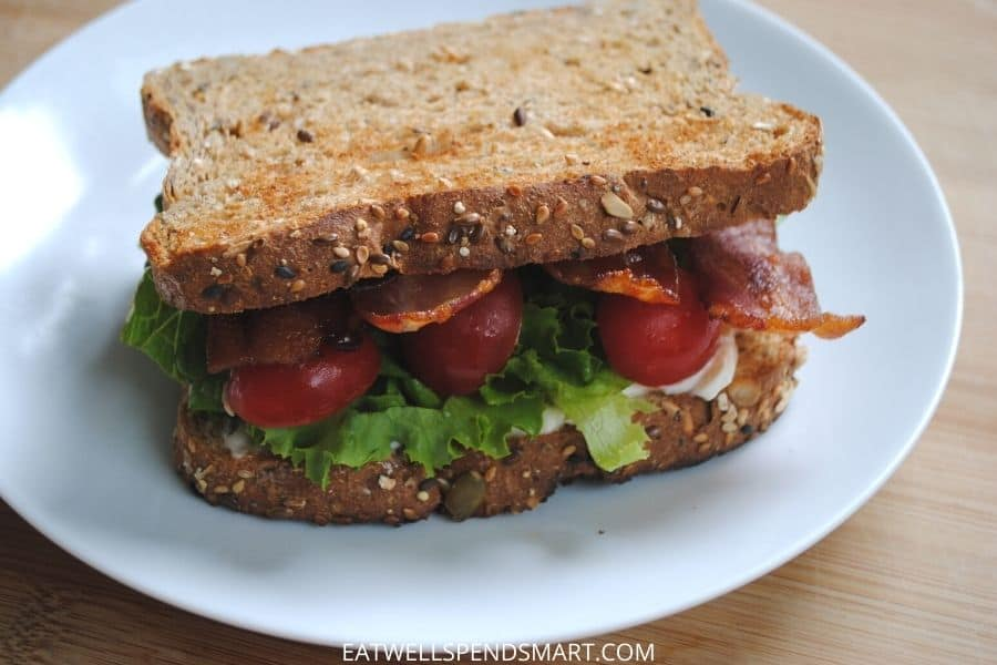 Bacon, lettuce, and tomato sandwich on a white plate
