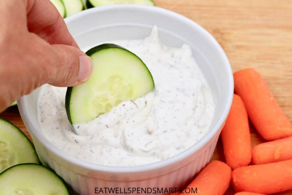 hand dipping a cucumber slice into a white bowl of sour cream dip