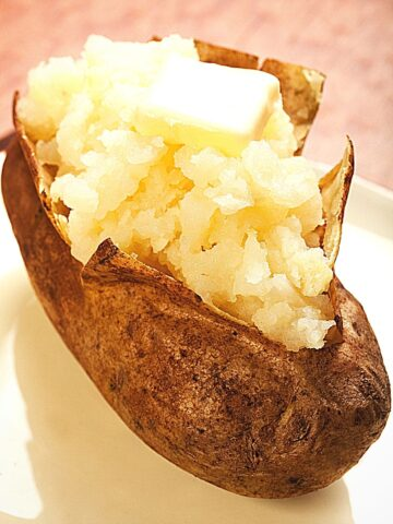 baked potato topped with butter on a white plate